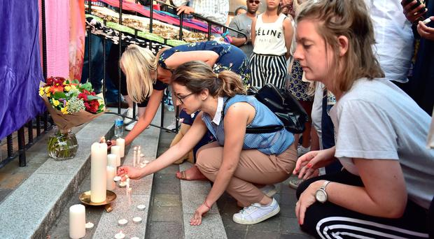 People light candles outside Notting Hill Methodist Church
