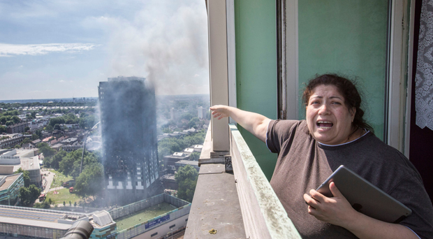 A distraught neighbour watches helplessly from a nearby tower block