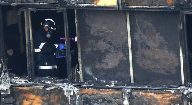 Fire service personnel survey the damage to Grenfell Tower (Rick Findler/PA)