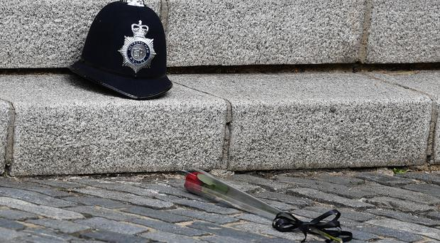 A single red rose in front of the police helmet of PC Keith Palmer (Ben Stansall/PA)