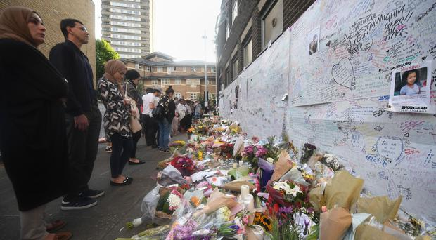 People look at tributes near Grenfell Tower (Victoria Jones/PA)