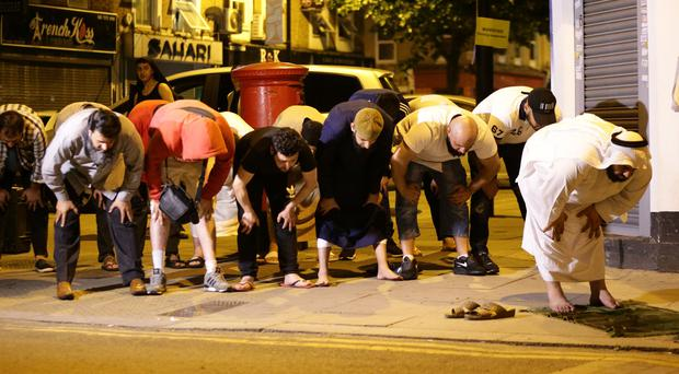 Local people observe prayers at Finsbury Park in north London, where one person has been arrested after a vehicle struck pedestrians (Yui Mok/PA)