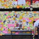 A British Red Cross volunteer reattachs a post-it note to a memorial wall underneath the Westway, near to the Grenfell Tower in west London, after a fire engulfed the 24-storey building on Wednesday morning (Jonathan Brady/PA)