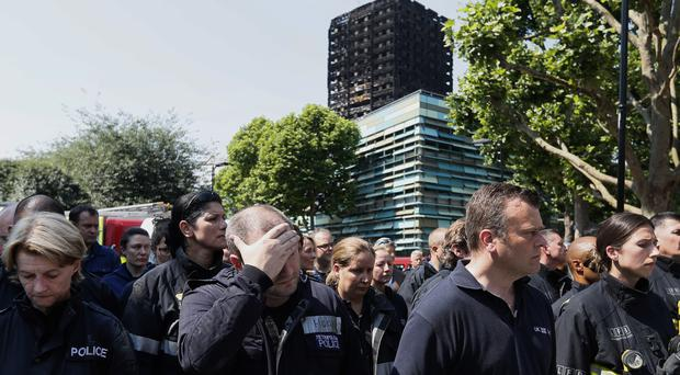 Emergency services workers observe a minute's silence in front of Grenfell Tower (Kirsty Wigglesworth/AP)
