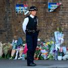 A policewoman stands beside floral tributes