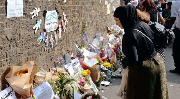 A woman leaves a floral tribute on Seven Sisters Road, close to Finsbury Park Mosque (John Stillwell/PA)