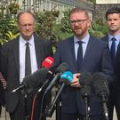 Senior DUP representative and former Stormont executive minister Simon Hamilton (centre) speaks to the media at Stormont Castle, Belfast (David Young/PA)