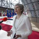 Theresa May speaks with the media as she arrives for an EU summit in Brussels (Virginia Mayo/AP)