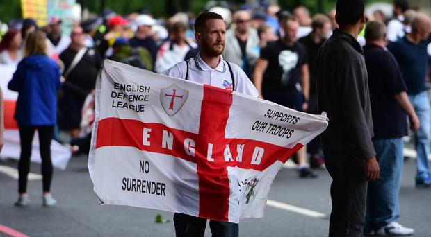 A man holds a flag during an English Defence League (EDL) protest in central London (David Mirzoeff/PA)