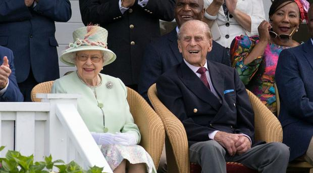 Queen Elizabeth II and the Duke of Edinburgh watch a British Driving Society parade during the Bentley Motors Royal Windsor Cup final (Steve Parsons/PA)