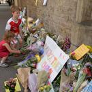 Two children lay flowers, close to Finsbury Park Mosque (John Stilwell/PA)