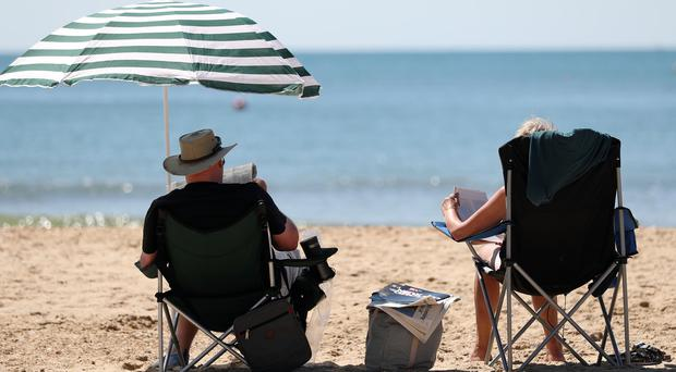People enjoying the warm weather on Boscombe Beach in Dorset (Andrew Matthews/PA)