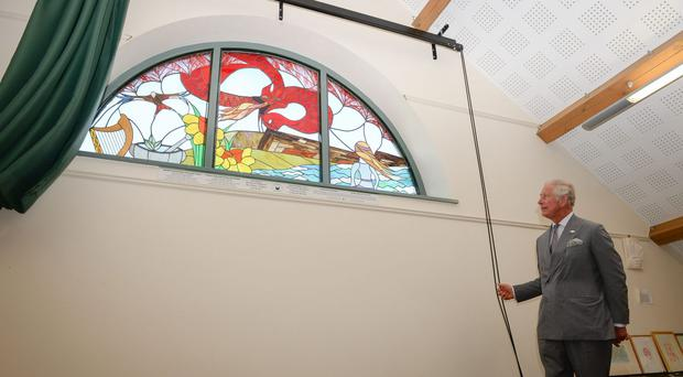The Prince of Wales unveils a new stained glass window on the theme of Welsh legends during his visit to Myddfai Community Hall in Wales (Ben Birchall/PA)