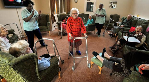 An elderly resident uses a zimmer frame to walk (John Stillwell/PA)