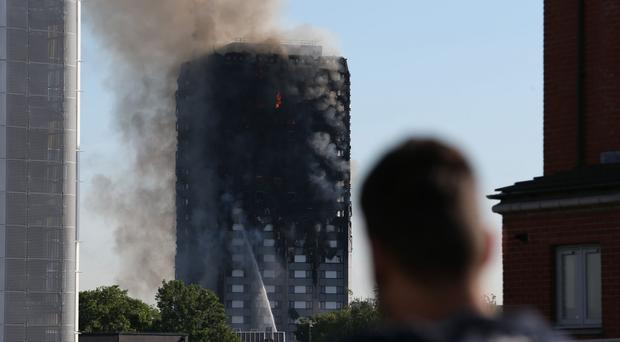 A man watches smoke rising from Grenfell Tower a month ago (Steve Paston/PA)