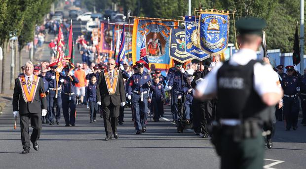 Orange Order members march past Ardoyne shops on the Crumlin Road in Belfast (Niall Carson/PA)