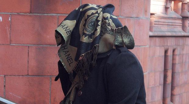Arafa Nassib covers her head with a scarf outside court (PA)