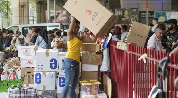 Volunteers organise boxes of donations for the Grenfell Tower fire victims (David Mirzoeff/PA)