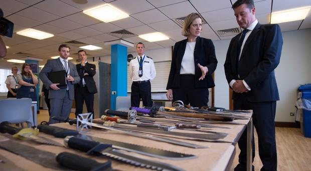 Amber Rudd is shown a collection of knives by Superintendent Sean Yates (Stefan Rousseau/PA)