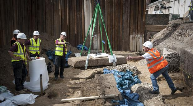 Archaeologists lift the lid of an ancient Roman sarcophagus dating from the 4th century (Lauren Hurley/PA)