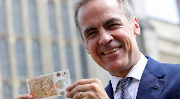 Mark Carney shows off the new banknote outside Winchester Cathedral (Steve Parsons/PA)