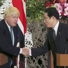 Boris Johnson shakes hands with Japanese counterpart Fumio Kishida (Koji Sasahara/AP)