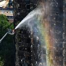 Firefighters spraying water after the blaze at Grenfell Tower (Victoria Jones/PA)