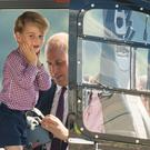Prince George stands in a rescue helicopter as his father adjusts a helmet for him to wear (Dominic Lipinski/PA)