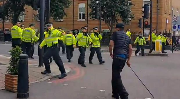 Police confront a protester in Kingsland Road in east London, where crowds gathered in response to the death of Rashan Charles (Spectrum Sino Radio/Twitter/PA)