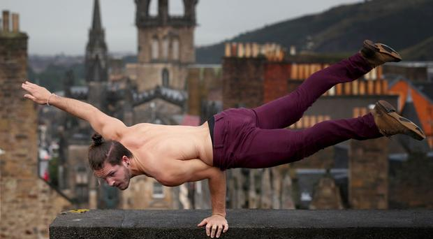 Cal Harris, a member of Head First Acrobats, balances on the roof of Camera Obscura and World of Illusions in Edinburgh, ahead of his Fringe Festival show Elixir (Jane Barlow/PA)