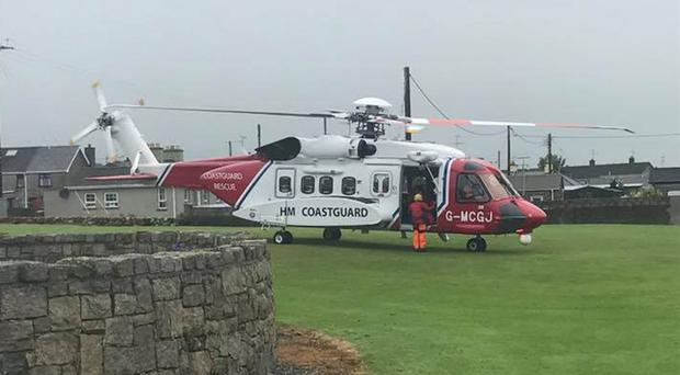 An HM Coastguard rescue helicopter lands in Annalong (Annalong Harbour Watch/PA)