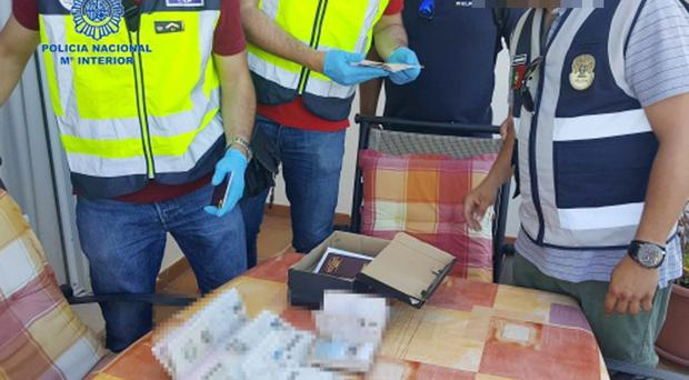 Spanish police with recovered fake passports and documents (Policia Nacional/PA)