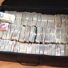 A suitcase full of cash was seized in a string of drugs raids in Merseyside (Merseyside Police/PA)