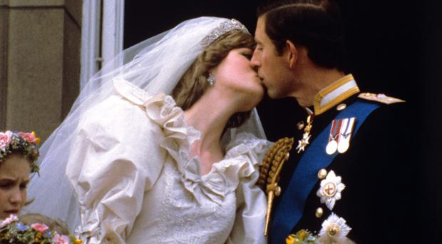 The Prince and Princess of Wales kissing on the balcony of Buckingham Palace after their wedding ceremony (PA)