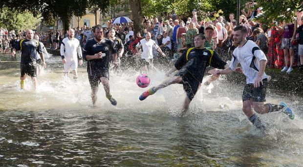 Teams from Bourton Rovers play each other in the annual traditional river football match in the Cotswolds village of Bourton-in-the-Water (Ben Birchall/PA)