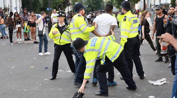 Police hold a man during the second and final day of the Notting Hill Carnival in west London ( John Stillwell/PA)