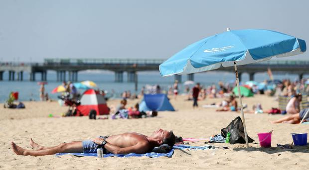 People sunbathe on Boscombe beach in Dorset (Andrew Matthews/PA)