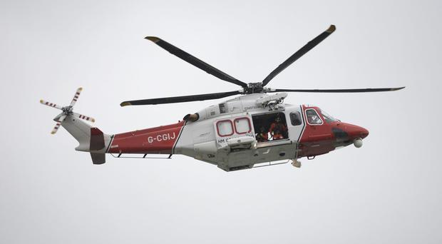 One man was recovered by a coastguard helicopter and taken to hospital (Andrew Matthews/PA)