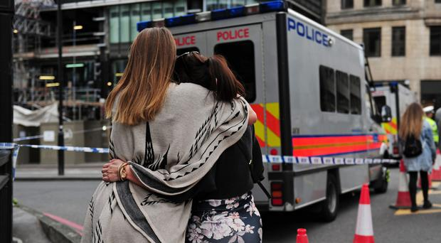 Two women hug after bringing flowers to add to tributes laid on the north side of London Bridge (David Mirzoeff/PA)