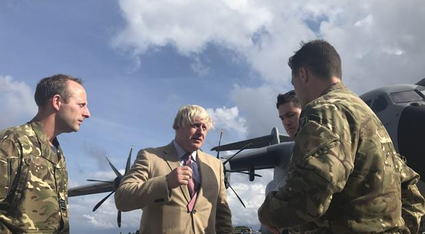 Foreign Secretary Boris Johnson talks to the pilots of an RAF A400M aircraft and Royal Marines from 40 Commando in Barbados (Georgina Stubbs/PA)