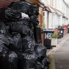 Rubbish bags are piled up in front of bins in Birmingham (Aaron Chown/PA)