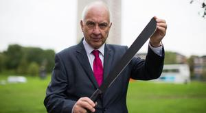 West Midlands Police and Crime Commissioner David Jamieson holds a machete, one of the weapons found in an amnesty bin (Aaron Chown/PA)
