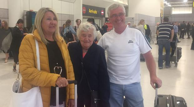 From left, Linda, Jean and Neil McConnohie, who arrived back in Manchester from Palma after they were repatriated (Eleanor Barlow/PA)