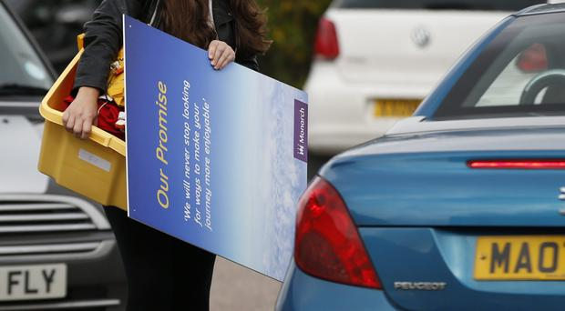 A member of Monarch Airlines cabin crew holds a poster advertising the airline as she carries her personal belongings to her car (Alastair Grant/AP)