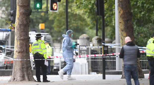 Police and a forensic officer at the scene after several people were injured when a car ploughed into people outside the Natural History Museum (Victoria Jones/PA)