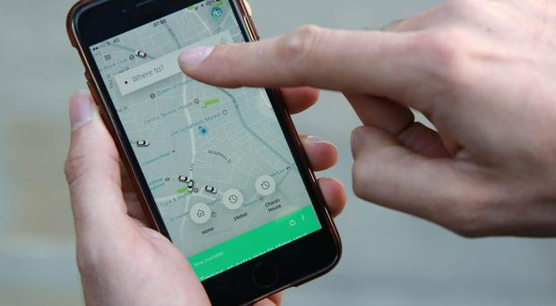 A man uses an Uber App on his mobile phone (PA)