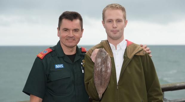 Sam Quilliam at Boscombe pier in Dorset where he was saved by paramedic Matt Harrison (left) (Ben Birchall/PA)