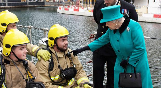 The Queen points to a piece of equipment on a fireman's jacket as she visits HMS Sutherland in London