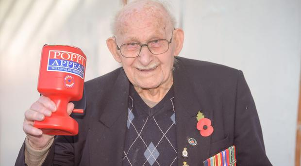 Ron Jones, who is 100 years old, holds his collection box outside a Tesco supermarket in Newport (Ben Birchall/PA)