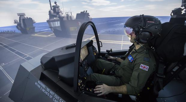 Royal Air Force Squadron Leader Andy Edgell, the UK's lead test pilot, uses a specialist fighter jet simulator at BAE Systems in Warton, Lancashire (Danny Lawson/PA)